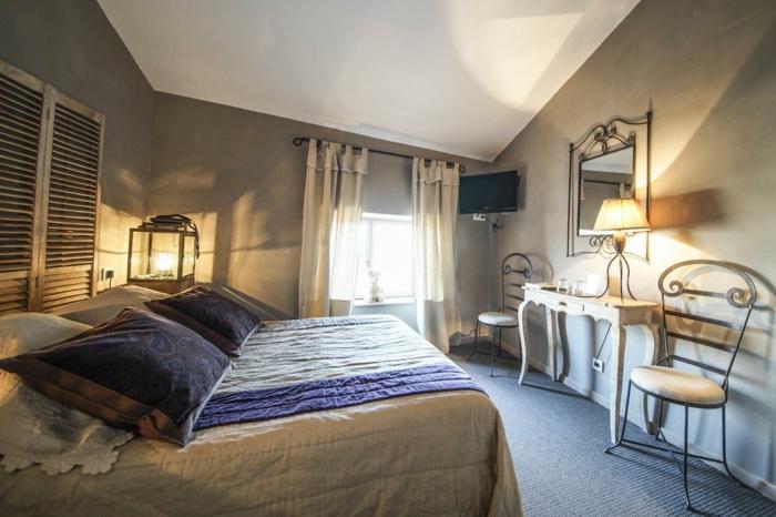 lanterne romantique dans une chambre à coucher, deux coussins noirs, chaise en fer forgé, table baroque