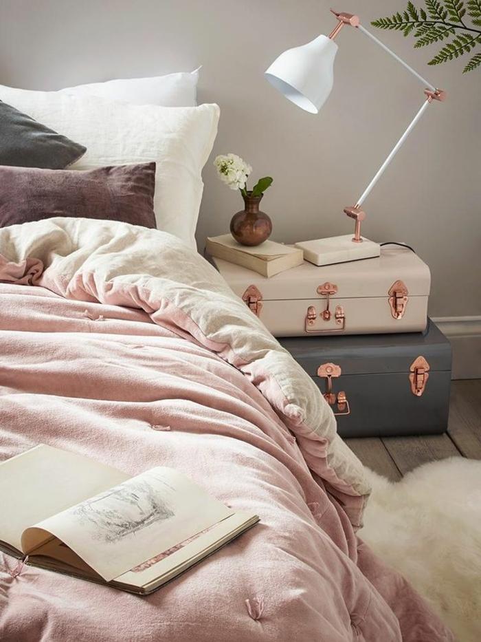 deux petites valises vintage avec des anses cuivrées, lampe de chevet élégante, plaid rose et fourrure blanche