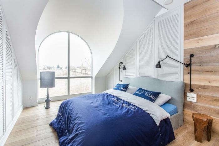 chalbre sous pente, lit avec parure bleue, appliques murales, tabouret tronc de bois