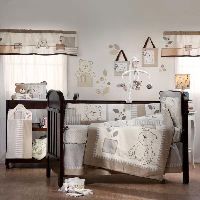 couleurs neutres dans la chambre bébé mixte avec plancher de bois et lit à barreaux noir, décoration des murs avec dessins et stickers à design ourson