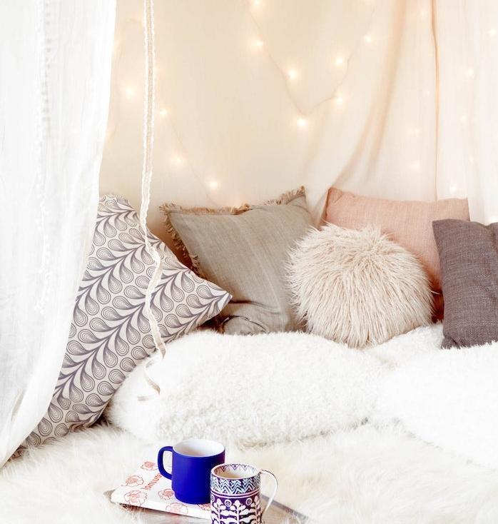 décoration hygge dans une chambre cocooning, fabriquer une tete de lit en guirlande lumineuse, coussins de lit décoratifs, voile blanche, linge de lit moelleux