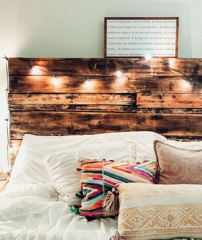 modele de tete de lit en palette de vois avec decoration de guirlande de noel, linge de lit blanc avec coussins décoratifs colorés style boheme chic