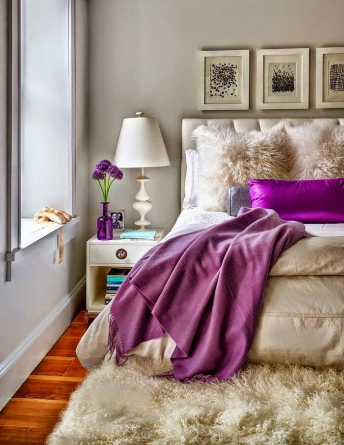 tapis blanc fausse fourrure, jeté de lit pourpre, chevet blanc, bouquet de fleurs lilas, murs gris pâles