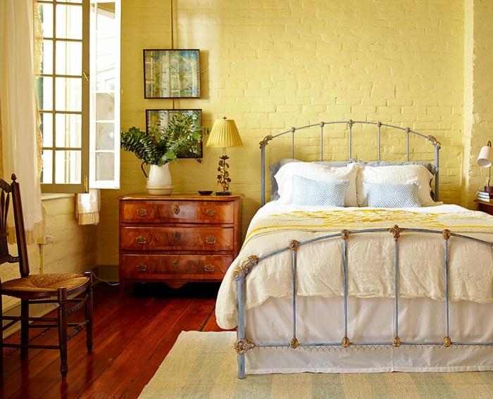 plancher en bois, lit vintage, mur en briques apparentes peintes jaunes, chaise rétro
