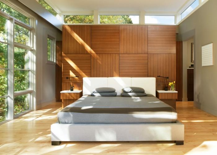 panneaux muraux de bois, lit avec grand matelas gris, fenêtres lumineuses, design de chambre minimaliste