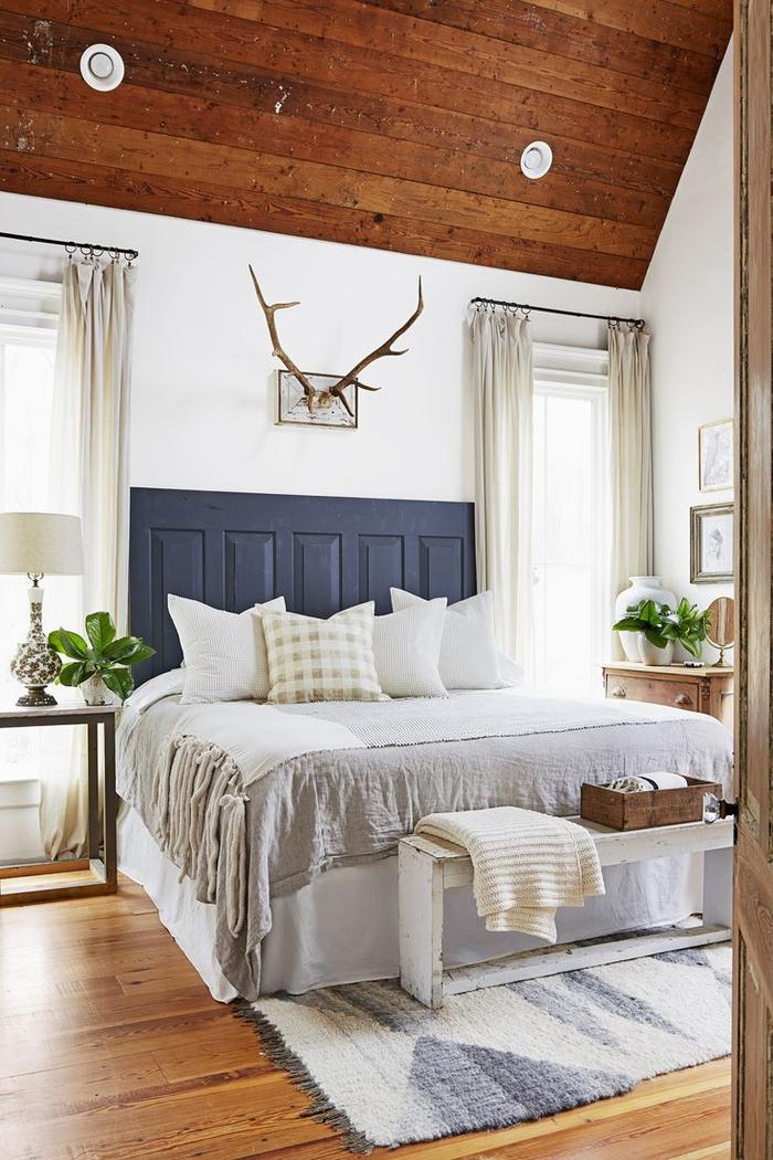 une chambre à coucher aménagée en style campagne chic avec un accent sur les textiles de luxe et tête de lit en bois récup, idée originale pour faire une tete de lit à partir d'une porte ancienne