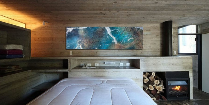 décoration chambre à coucher, poêle rustique et range bûches, tableau abstrait