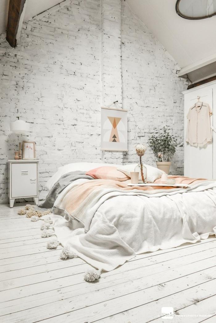 lit bas, linge de lit pompons, mur en briques, sol en planches blanches, intérieur tout blanc
