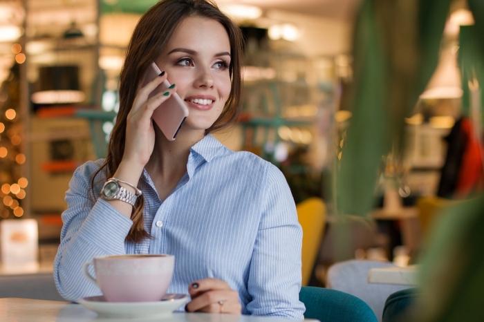 jeune femme d'affaire aux cheveux brun et maquillage élégant avec eye-liner et rouge à lèvres marron