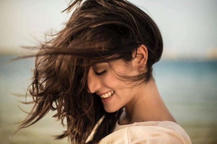 vision naturelle et belle aux cheveux longs et raids de nuance châtain foncé aux reflets cendrés, promenade au bord de la mer femme