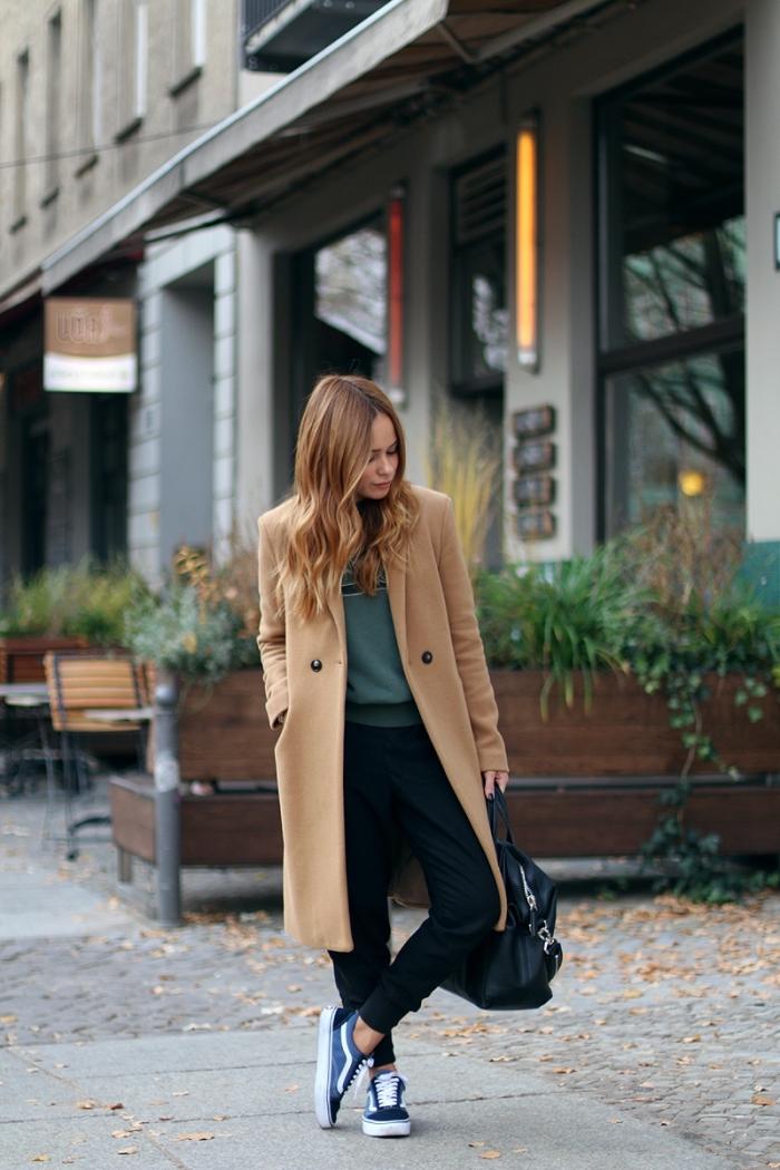 vision chic urbain en pantalon noir slim et blouse vert foncé combiné avec un manteau long élégant de nuance beige