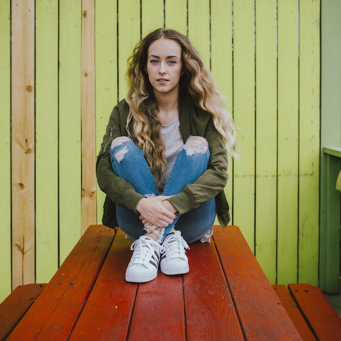 exemple de coupe de cheveux ado fille, cheveux blond longs avec de gros boucles, jean et veste kaki