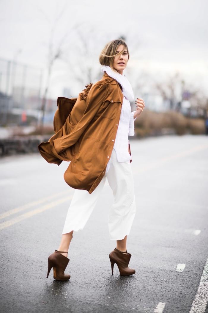 femme habillée en veste camel longue, s'habiller en blanc avec un pantalon fluide blanc et une chemise loose blanche, manteau camel foncé et bottines marron