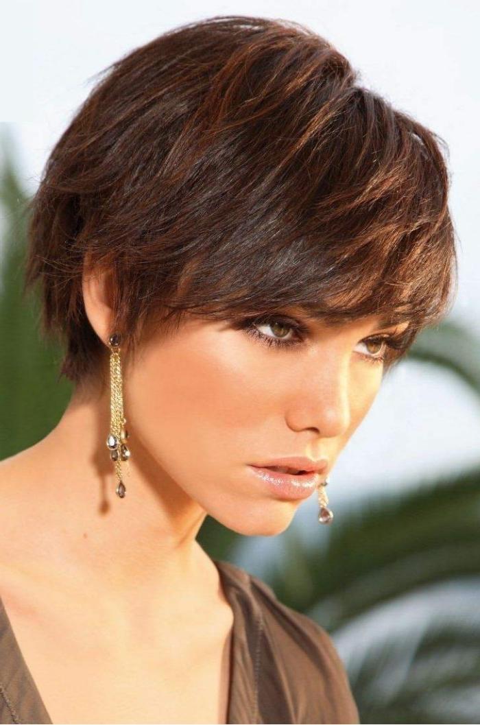 coiffure cheveux court avec frange effilée à porter avec boucles d'oreilles pendantes et maquillage yeux foncés