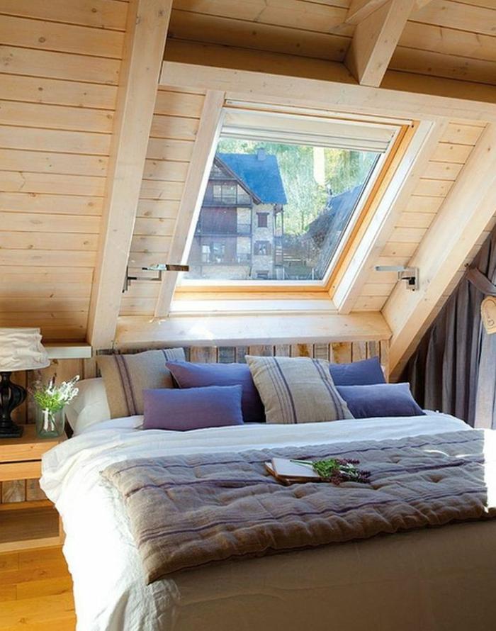 comble aménagé, plafond en bois, lit avec plusieurs coussins, fenêtre en pente