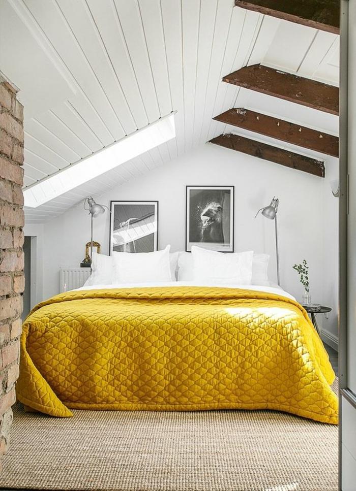 mur en briques rouges, lit avec parure jaune, poutres en bois, plafond et murs blancs, comble aménagé