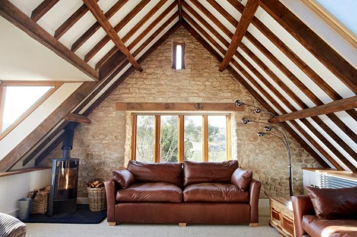 mur de briques authentiques, sofa en cuir, poutres de bois au plafond, poêle rustique; combles aménagés