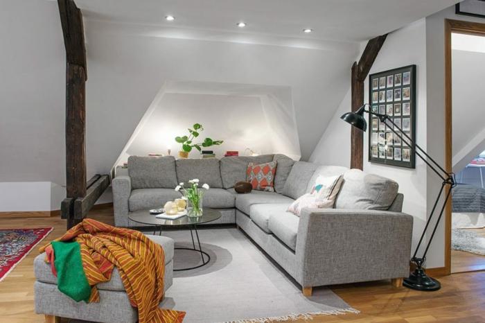 salle de séjour scandinave, sofa gris d'angle, tapis gris, tabouret gris avec des plaids vives, plancher en bois