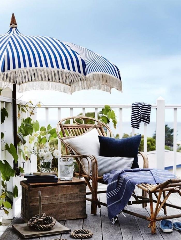 décoration pour balcon cosy, meubler sa terrasse avec meubles en bois vintage, parasol bleu et blanc pour balcon