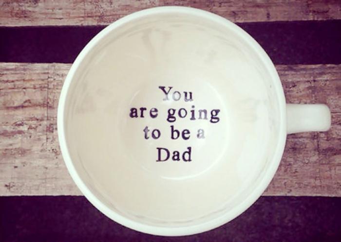 tu seras un père ou comment annoncer une grossesse, une tasse blanche avec un script au fond