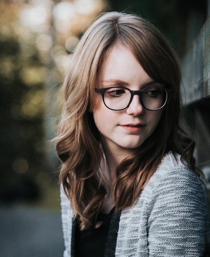 exemple classique de coupe de cheveux ado fille en dégradé avec de diverses longueurs et des ondulations, lunettes de vue hipster