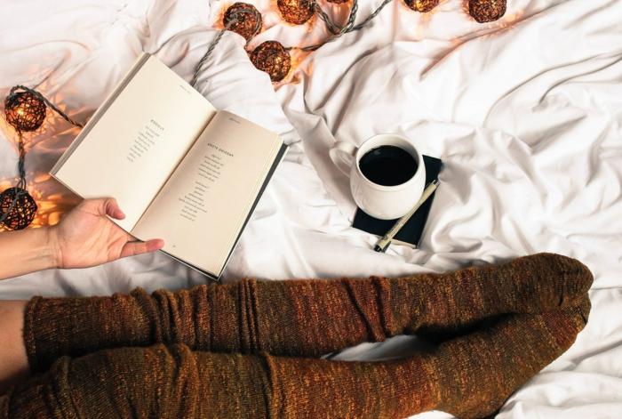 chaussettes marrons hautes, guirlande cocooning, tasse de café, livre de poésie