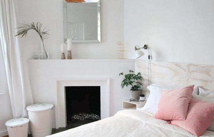 déco douce et féminine dans une chambre à coucher épurée meublée avec un lit à tete de lit bois en contreplaqué