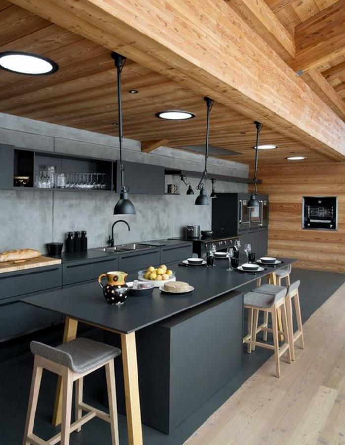pièce avec des meubles en gris anthracite, repeindre sa cuisine, plafond avec des poutres en bois massif, sol avec parquet en gris, tabourets de bar en gris pastel avec des pieds en bois clair