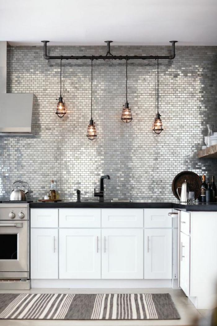 renover sa cuisine, repeindre meuble cuisine, mur brillant recouvert avec des feuilles brillantes en couleur argent, tapis rectangulaire en gris et rose pastel, luminaires en métal noir, quatre ampoules en verre transparent