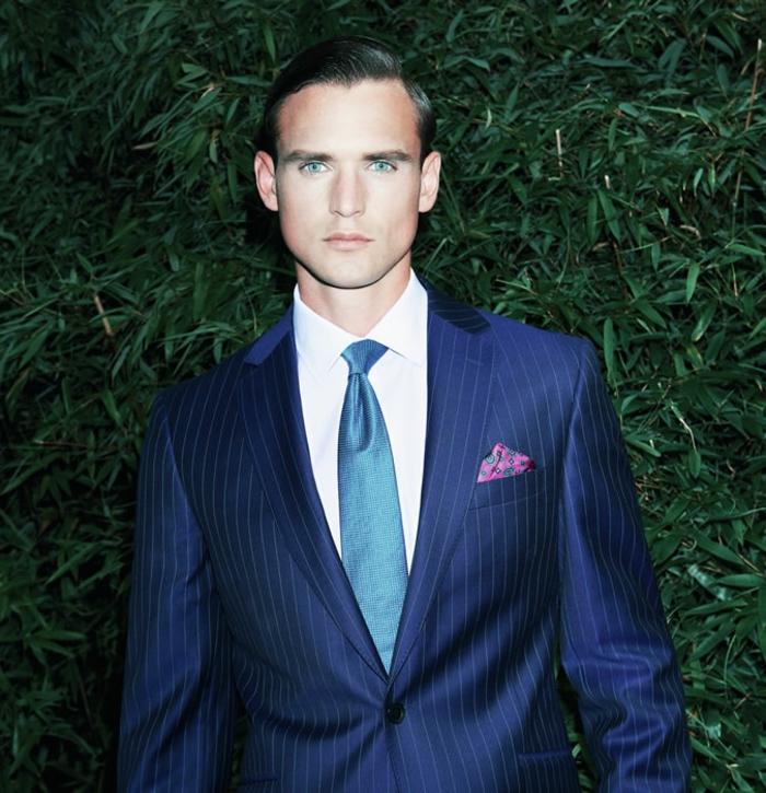 cravate bleu ciel, costume hugo boss, chemise blanche, costume bleu roi, mouchoir de poche veste en fuchsia et bleu turquoise, veste avec un seul grand bouton en noir , costume aux rayures fines blanches