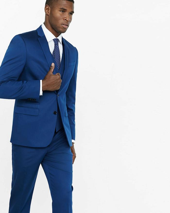 costard bleu avec chemise banche et cravate bleue a pois blancs, pantalon moulant les jambes, look de business homme