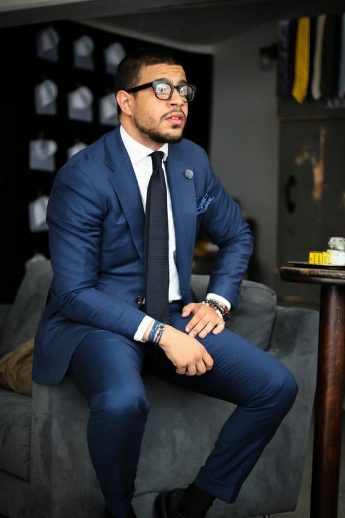 veste costume homme en bleu royal, cravate noire, chemise blanche, chaussures noires, lunettes grandes montures noires