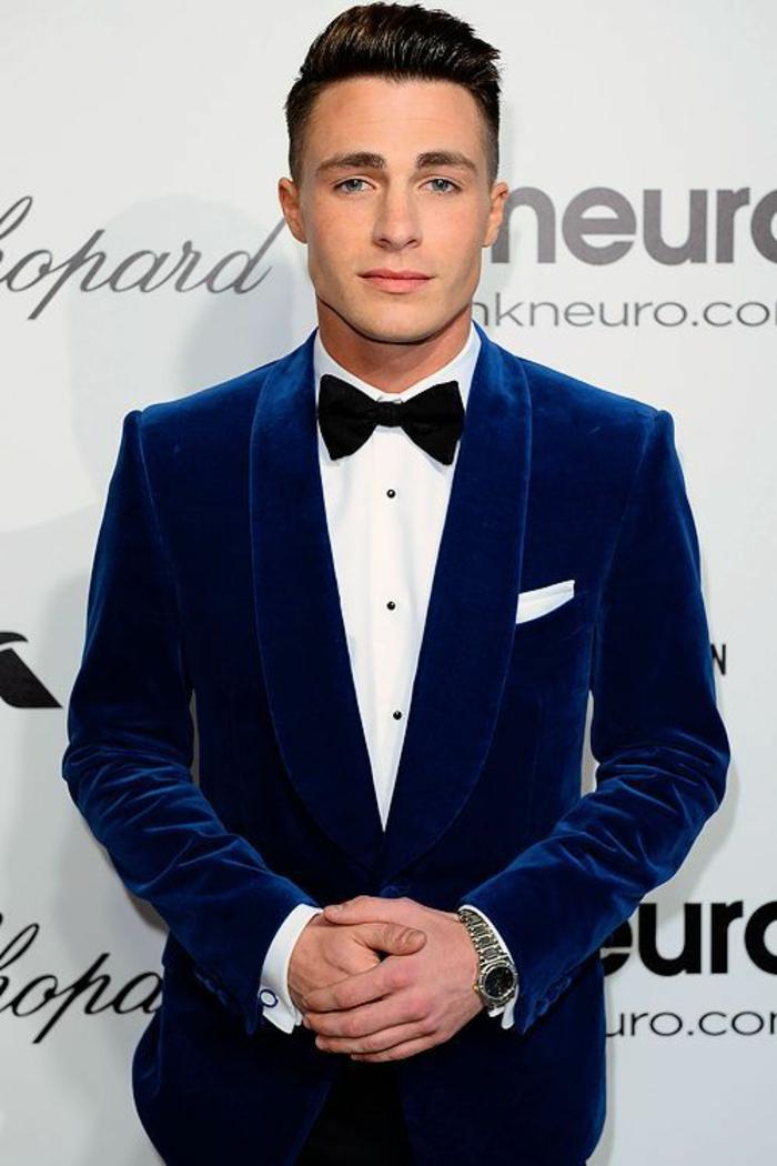 costard bleu avec veste en velours, chemise blanche avec nœud papillon noir, mouchoir blanc dans la poche, montre métallique
