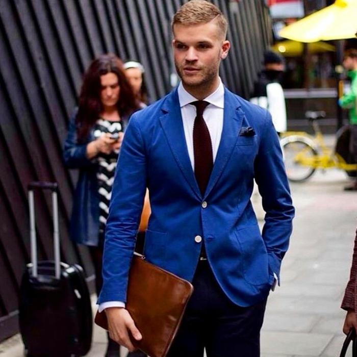 veston homme avec deux boutons, look décontracté, pantalon en bleu marine, sac-pochette pour les documents en marron clair, cravate en bordeaux, mouchoir de poche en bleu nuit, nuance foncée du bleu