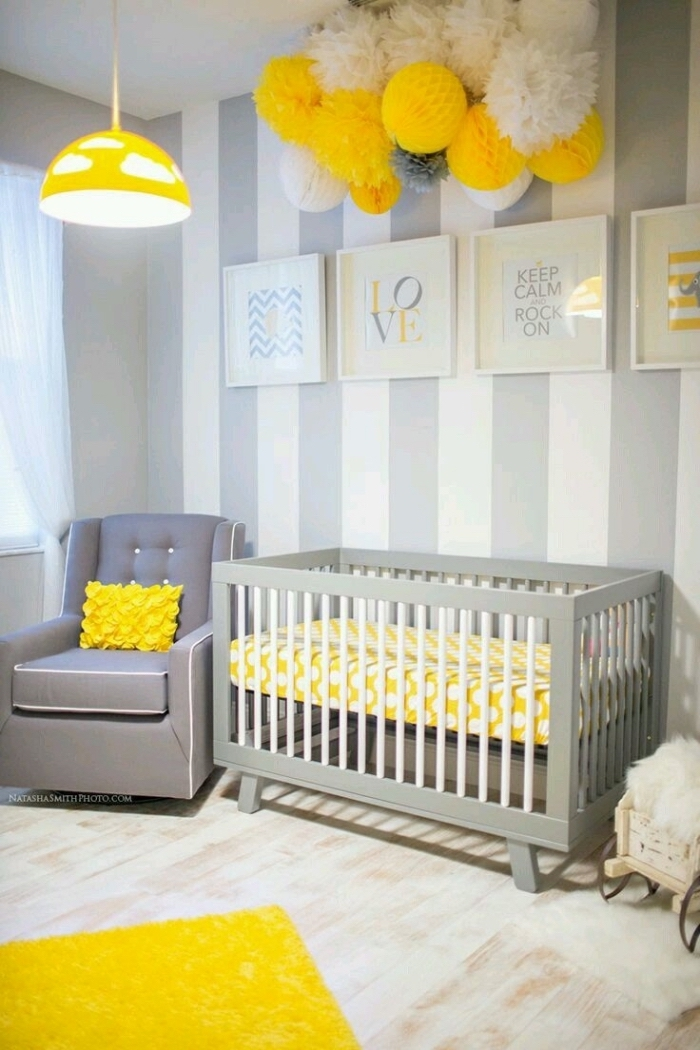 exemple de chambre bebe complete avec fauteuil boutonné gris et lit à barreaux, lampe et tapis jaune dans la chambre gris et blanc
