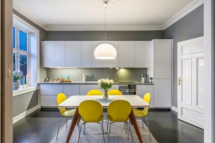 mur repeint de peinture grise, meuble de cuisine gris, suspension blanche, sol gris et ouverture sur salle à manger en chaises jaunes et table blanche