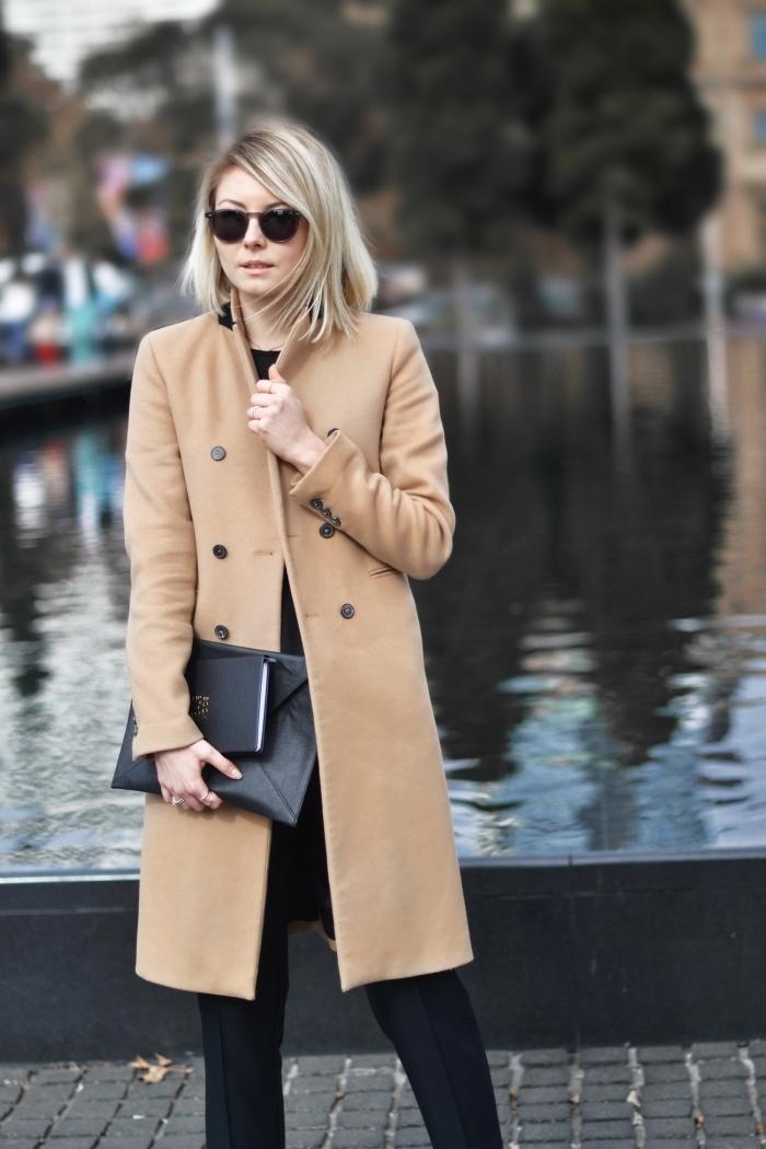look total noir en pantalon blouse et sac à main noirs combinés avec modèle de manteau long beige à boutons noirs