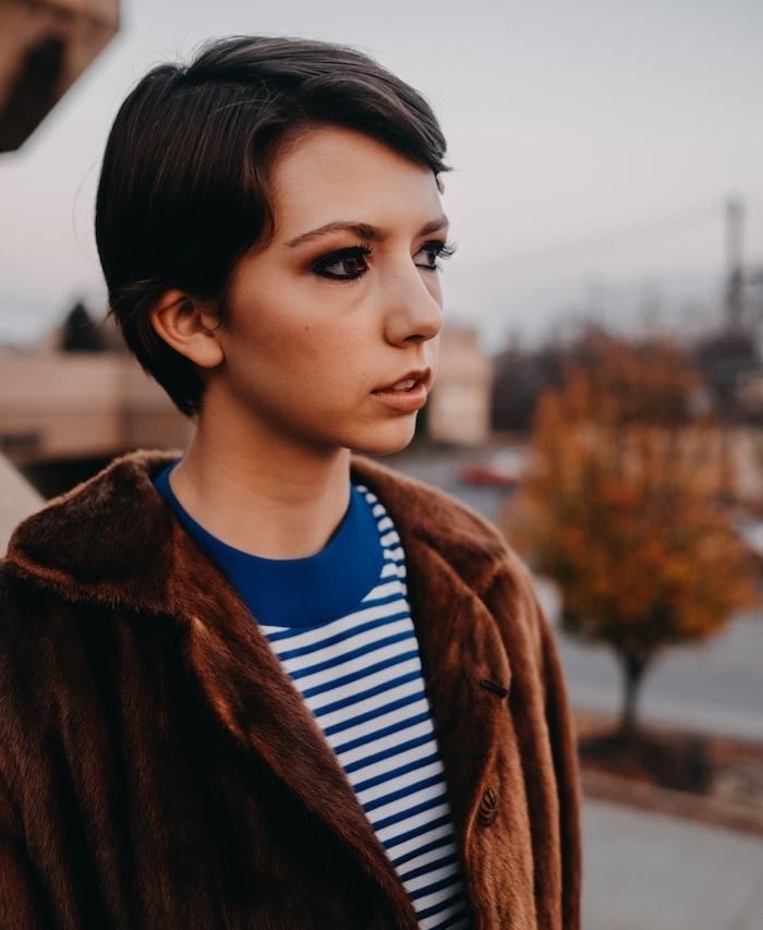 coupe ado courte avec frange sur le coté, veste femme marron, chemise à rayures bleu et blanc, modele de coupe pixie