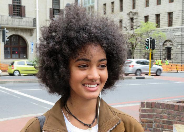 jeune femme metisse avec cheveux bouclés afro mi long et piercing nez