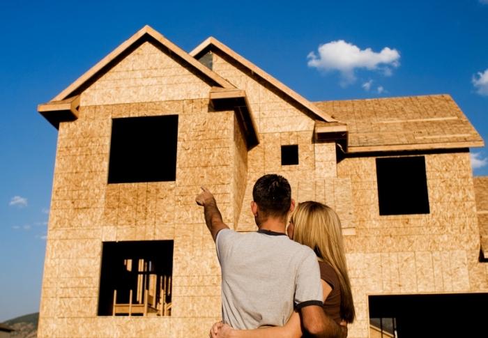 couple devant le chantier de leur maison construite avec l'assistance d'un architecte du bâtiment