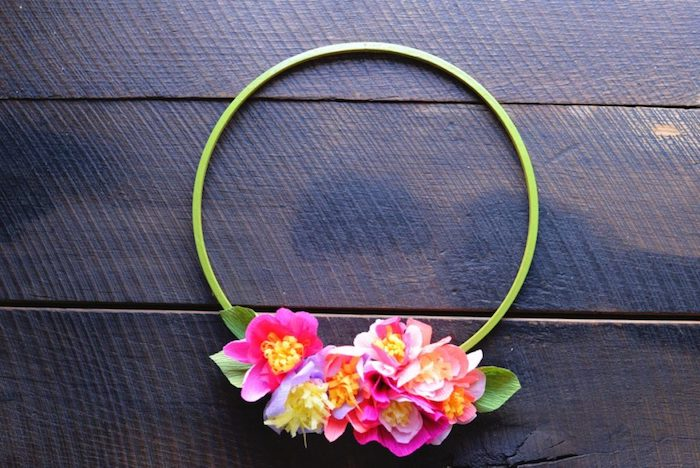 idée d activité manuelle pour fabriquer une couronne de fleurs en anneau vert en plastique et fleurs colorés en papier crépon