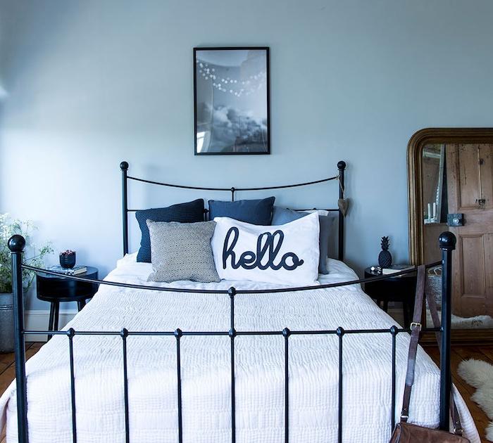 mur couleur bleu de gris, coussins gris et bleu marine et blancs, linge de lit blanc, lit metallique vintage, grand miroir avec cadre en bois, table de nuit noire