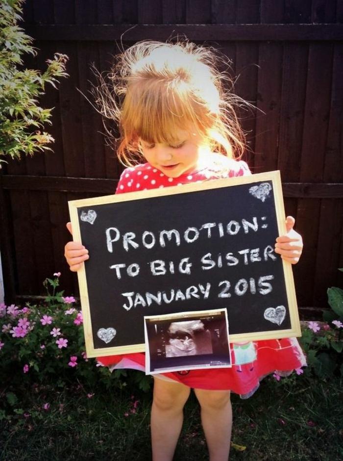 la soeur aînée qui tient un tableau promotion en soeiur aînée, faire un annonce de grossesse original
