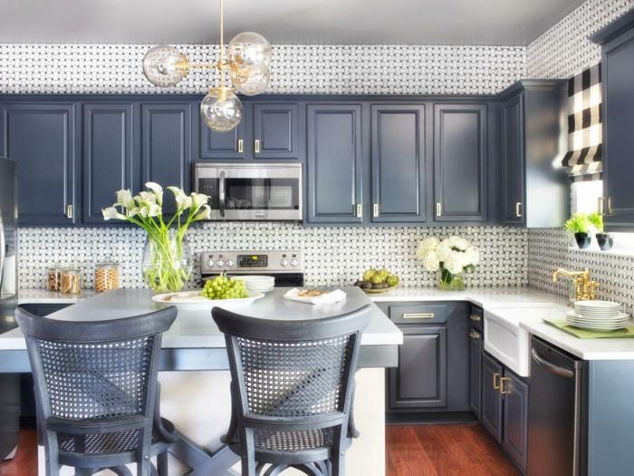 armoires de cuisine en gris perle, chaises en gris perle, luminaire en forme de quatre boules en verre transparent, carrelages muraux en blanc et gris sur les murs au-dessus des fourneaux et au-dessus du lavabo