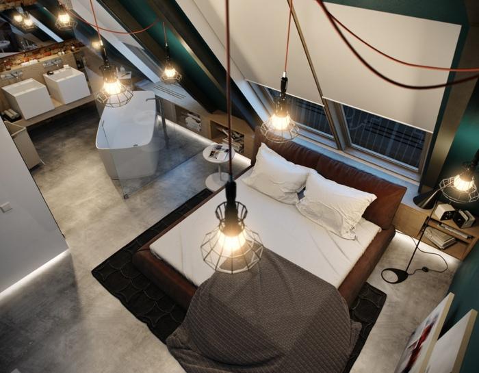 baignoire blanche, lit, suspensions industrielles cages, sol en béton ciré, chambre et salle de bain