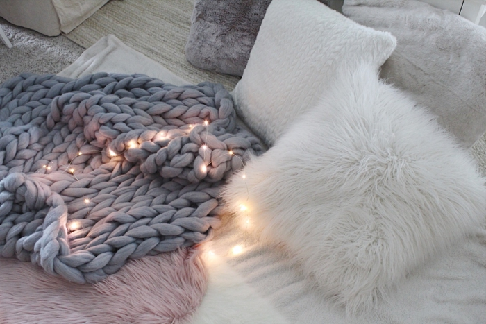petites lampes allumées, matières moelleuses, coussins blancs, déco cosy