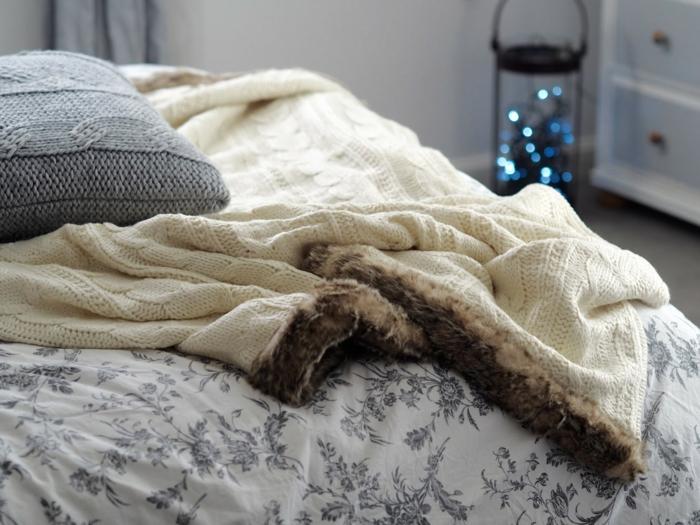 coussin tricot, plaid beige, linge de lit beige, lanterne décorative, placard blanc