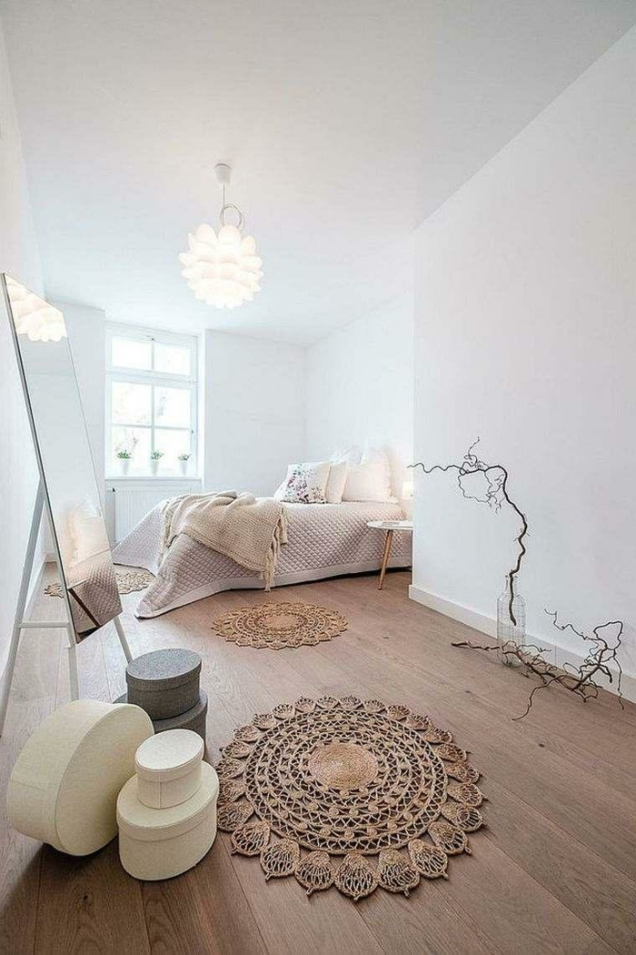 petit tapis boho, sol en planches de bois, murs blancs, plafonnier à plusieurs lamelles, miroir autoportant