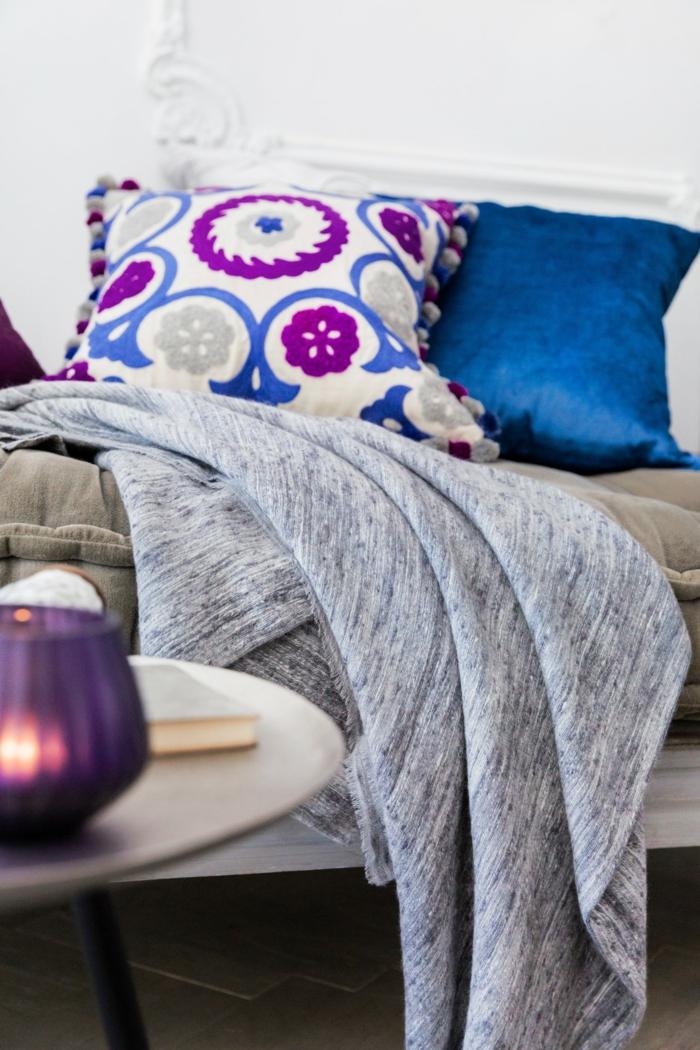 lit cocooning, table blanche ronde, décoration chambre à coucher, coussins en bleu, lilas et blanc