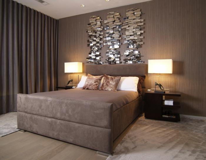 panneau mural brillant, lit taupe, tapis taupe, deux chevets avec lampes, rideaux lourds